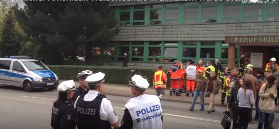 Phụ huynh chờ đợi và cảnh sát giữ trật tự trước cổng trường dậy nghề, nơi sơ tán học sinh của trường Elmshorner Waldorf.