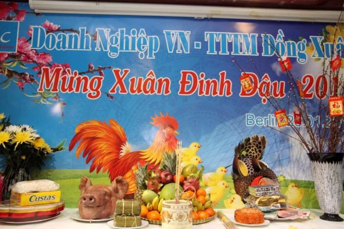 Mâm cỗ Tết được trình bày khá đẹp bên tấm phông năm con gà của buổi lễ đón Tết.