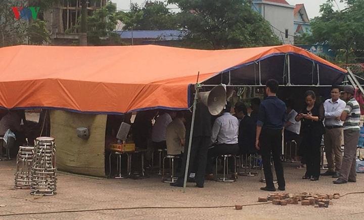 Tại một lều dã chiến được dựng trong sân nhà văn hóa thôn Hoành, ông Nguyễn Đức Chung ký nhận bản cam kết với xã Đồng Tâm
