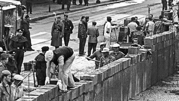 Lúc đầu bức tường chỉ được xây bằng gạch, thậm chí bằng dây thép gai