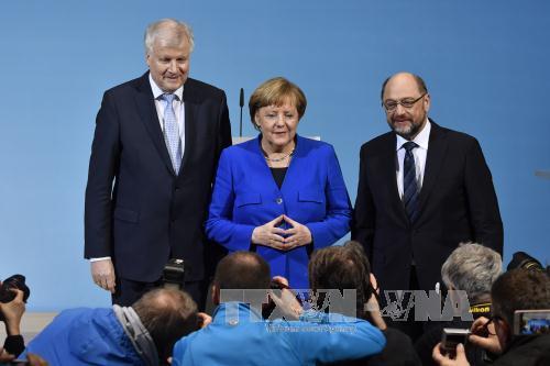 Thủ tướng Đức Angela Merkel (giữa) trong cuộc họp báo tại Berlin ngày 12/1. Ảnh: AFP/TTXVN